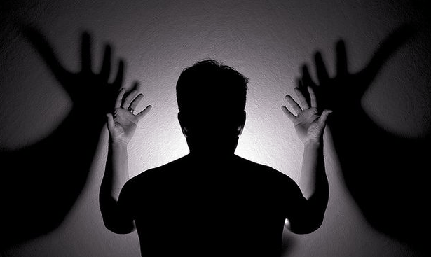 man raising his hands as shadows on the wall